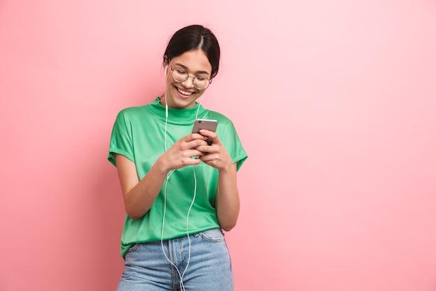 Ragazza europea che indossa occhiali rotondi utilizzando gli auricolari mentre si tiene lo smartphone isolato su una parete rosa