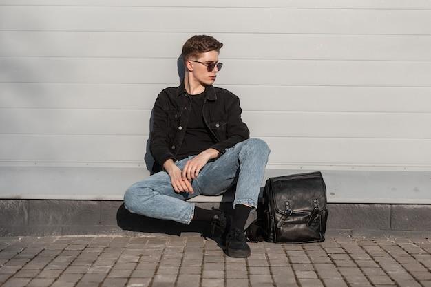 Giovane europeo con occhiali da sole neri in eleganti vestiti casual in denim con scarpe da ginnastica alla moda