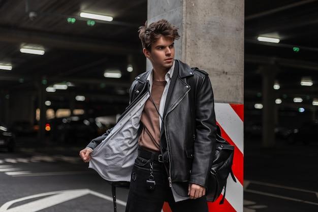 Giovane europeo in una giacca di pelle nera alla moda in una camicia classica con uno zaino vintage con un'acconciatura in posa vicino a un pilastro con una linea rosso-bianca in un parcheggio cittadino. ragazzo attraente alla moda