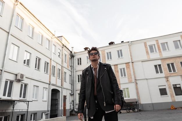 Il giovane europeo in abiti di pelle oversize della moda giovanile con un'acconciatura alla moda sta riposando vicino a edifici moderni della città in una giornata primaverile. pantaloni a vita bassa del ragazzo moderno in occhiali da sole alla moda all'aperto.