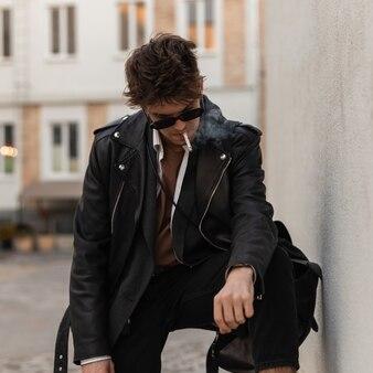 Hipster europeo giovane con acconciatura in occhiali da sole in giacca nera elegante in pelle in jeans si leva in piedi e fuma vicino a un muro vintage sulla strada. bel ragazzo gode di fumare all'aperto. pausa sigaretta.