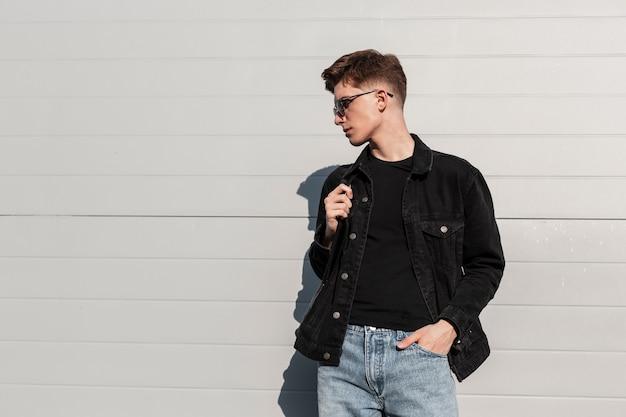 Giovane europeo con occhiali da sole alla moda in eleganti vestiti casual in denim per giovani con zaino in pelle alla moda