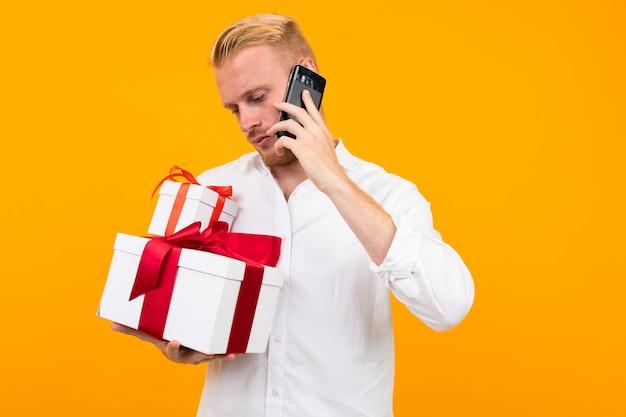 Il giovane europeo in una camicia bianca tiene un contenitore di regalo b sta parlando al telefono su un giallo.