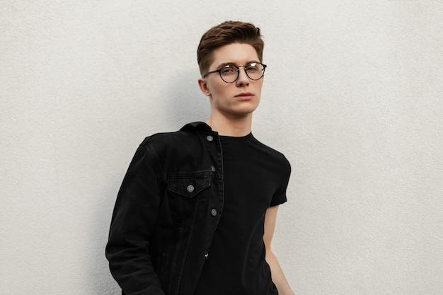 Il giovane europeo con l'acconciatura in maglietta alla moda in giacca di jeans alla moda in occhiali vintage sta riposando vicino all'edificio in città. ragazzo attraente modello di moda in abiti giovanili sulla strada.