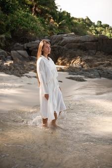 Le giovani donne abbronzate europee riposano e corrono sulla spiaggia di sabbia bianca. lunghi capelli castani neri. vestiti di cotone bianco. abito in stile boho. thailandia. mare cristallino acquamarina