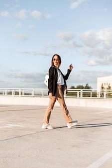 La giovane donna europea in vestiti alla moda di affari dalla nuova collezione in occhiali da sole in scarpe alla moda cammina sull'asfalto all'aperto il giorno di estate soleggiato. la ragazza alla moda urbana viaggia sul parcheggio