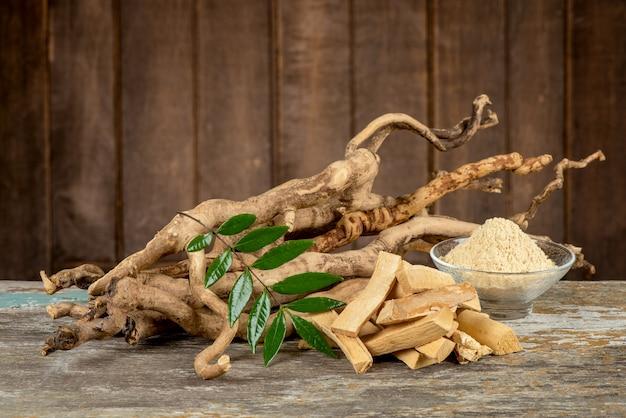 Eurycoma longifolia jack, radici essiccate, foglie verdi e polvere su un vecchio sfondo di legno.