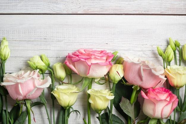 Fiori di eustoma e rose rosa su fondo in legno in stile vintage. vista dall'alto. cornice e copia spazio
