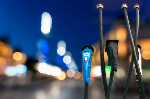Stazione di ricarica per auto ev con uno sfondo di luci sfocate dell'auto