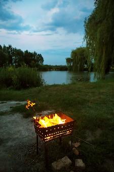 Legna da ardere alla brace alla sera, preparazione per la frittura di carne, vicino al lago