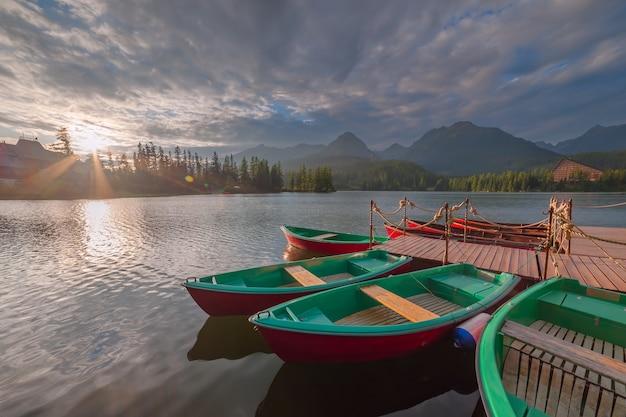 Paesaggio serale con barche sull'acqua e sulle montagne. bellissimo lago in alti tatra. strbske pleso, slovacchia