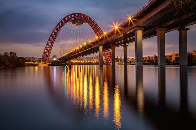 Luci della sera su un pittoresco ponte, che si riflette nel fiume di mosca.