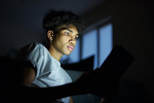 Ritratto di routine serale di un giovane concentrato che legge un e-book utilizzando un tablet pc di notte seduto dentro