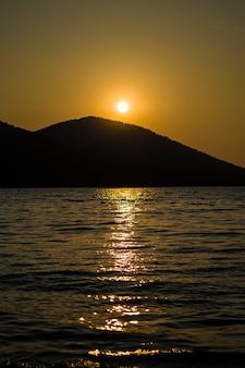 Tramonto serale dietro la montagna su un grande lago romantica vista del tramonto sul lago tra le...