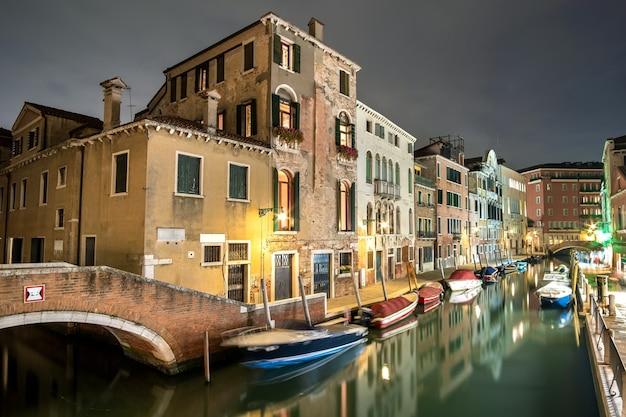 Vista serale di vecchi edifici illuminati, ponti, barche galleggianti e riflessi di luce nell'acqua dei canali a venezia, italia.