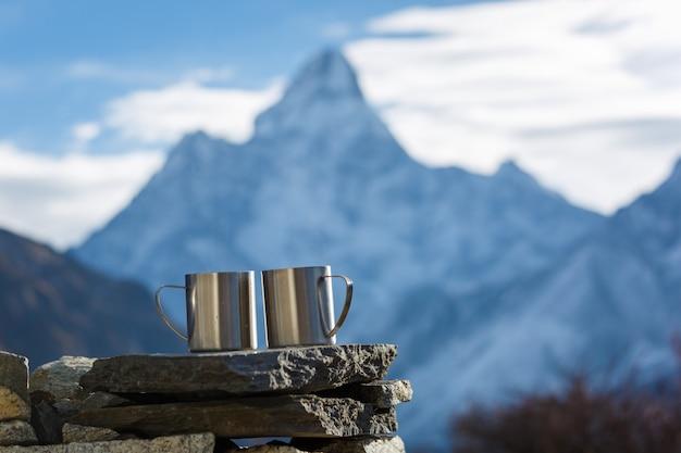 Escursione al campo base dell'everest. due tazze di tè sullo sfondo del monte ama dablam a fuoco. sfondo di montagne sfocato.