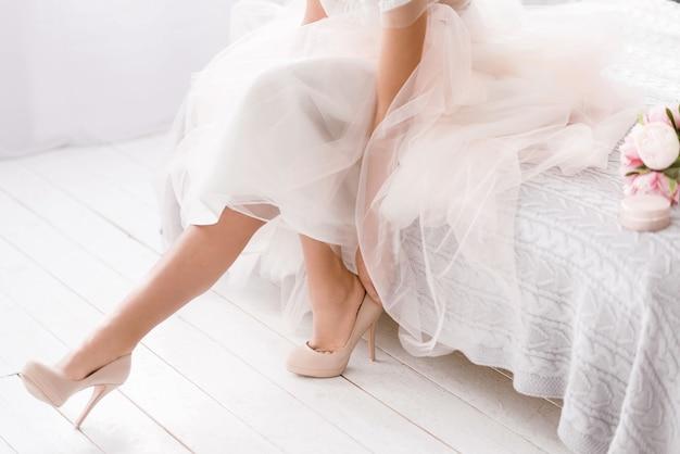 Ogni dettaglio è importante. affascinante e piacevole giovane sposa seduta sul letto in camera di colore bianco mentre indossa le sue scarpe ed esprime tenerezza