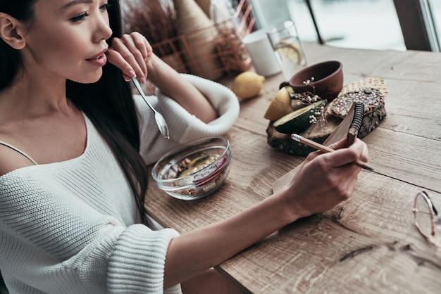 Routine quotidiana. vista dall'alto di una giovane donna attraente che mangia una sana colazione