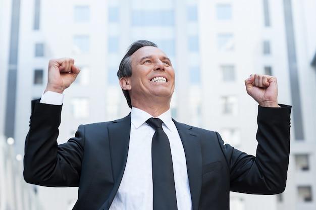 Vincitore di tutti i giorni. felice uomo anziano in abiti da cerimonia che tiene le braccia alzate ed esprime positività stando in piedi all'aperto