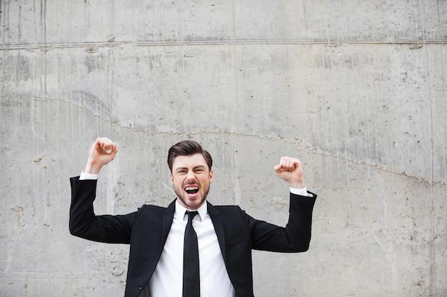 Vincitore di tutti i giorni. felice giovane in abiti da cerimonia che tiene le braccia alzate ed esprime positività stando in piedi contro il muro di cemento