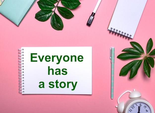 Tutti hanno una storia è scritta in verde su un blocco note bianco su uno sfondo rosa circondato da blocchi per appunti, penne, sveglia bianca e foglie verdi
