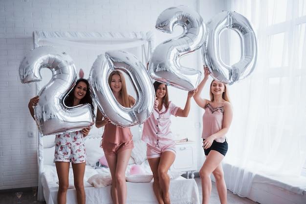 Tutti sorridono. quattro ragazze in abiti rosa e bianchi stanno con palloncini color argento. concezione di felice anno nuovo