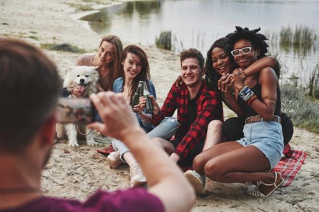 Tutti guardano nella telecamera. un gruppo di persone fa un picnic sulla spiaggia. gli amici si divertono durante il fine settimana.