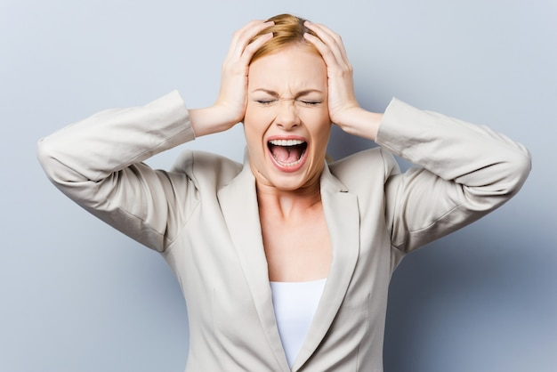 Tutto va male! bella giovane donna d'affari che urla e tiene la testa tra le mani mentre sta in piedi su uno sfondo grigio