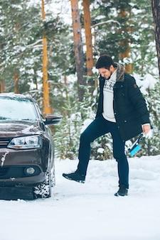 Il malvagio guidatore prende a calci il volante di un'auto in inverno nei boschi