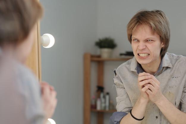 Giovane malvagio con lenti a contatto da vampiro negli occhi che sogghignano davanti allo specchio