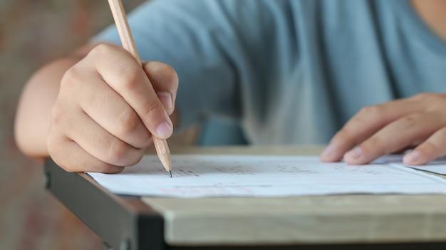 Esame test scuola o concetto universitario: studente a mano che tiene la matita che scrive risposta standardizzata a più moduli di carta carbone con foglio risposte nero grigio bollito facendo la valutazione finale in classe