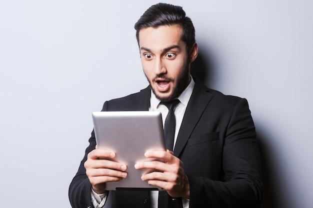 Esaminando il suo tablet nuovo di zecca. giovane sorpreso in abiti da cerimonia che tiene in mano un tablet digitale mentre si trova su uno sfondo grigio