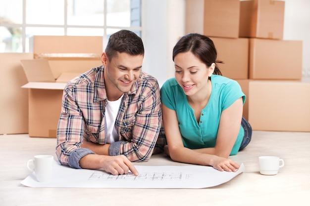 Esame di un piano di casa. allegra giovane coppia sdraiata sul pavimento e guardando il progetto mentre scatole di cartone posano sullo sfondo
