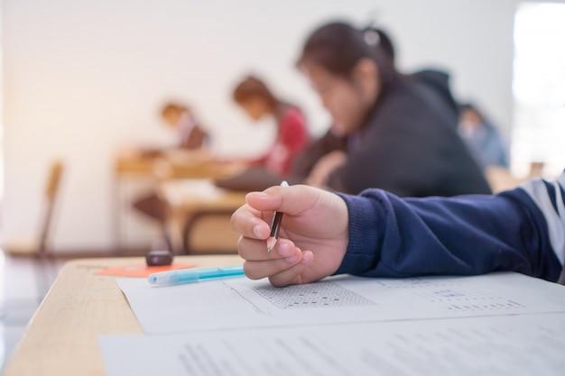 Studente di prova esami in liceo, studente universitario in possesso di matita per testare foglio di risposta esame