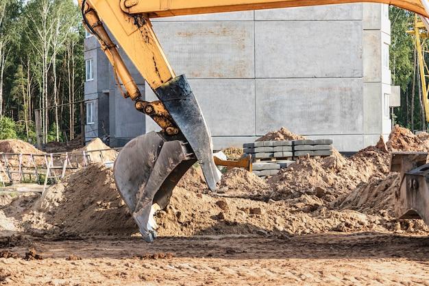 Benna dell'escavatore da vicino. lavori di scavo in cantiere e costruzione di strade. macchine da cantiere.
