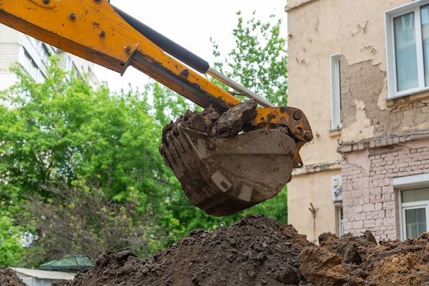 La benna dell'escavatore versa il terreno