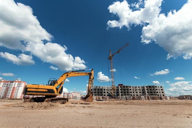 Escavatore in un cantiere sullo sfondo di una gru a torre