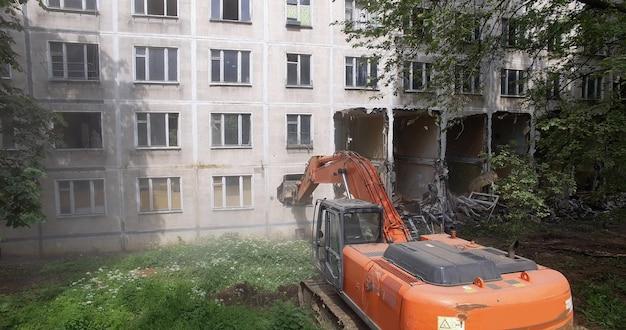 Un escavatore distrugge l'edificio con la sua benna