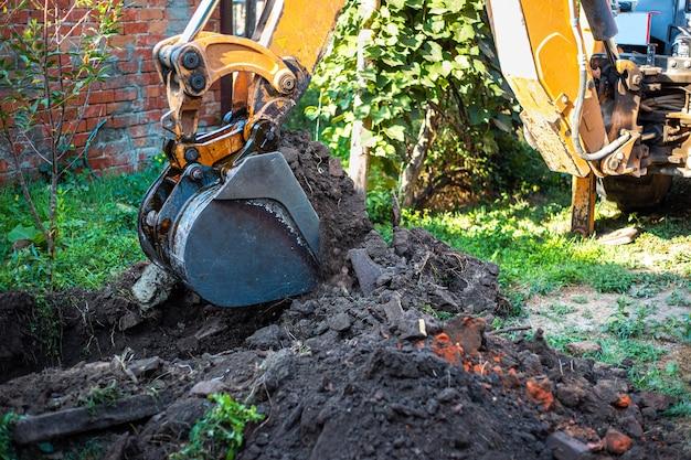 L'escavatore scava il terreno con un grande secchio sul terreno per posare un sistema di approvvigionamento idrico.