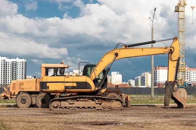 L'escavatore e la livellatrice stanno fianco a fianco contro il cielo azzurro. macchine movimento terra per costruzioni pesanti. costruzione di strade e comunicazioni sotterranee. industria di costruzioni.