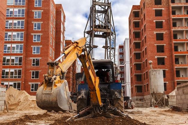 L'escavatore livella il terreno in un cantiere edile