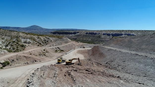 Escavatore carico camion di pietre, nella costruzione di strade.