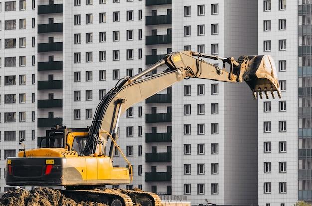 Escavatore lavora a terra su sfondo di case a più piani.