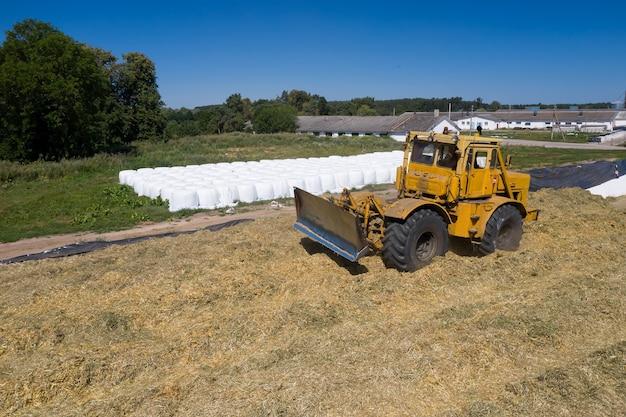 Escavatore che lavora su un mucchio di insilato nella fattoria