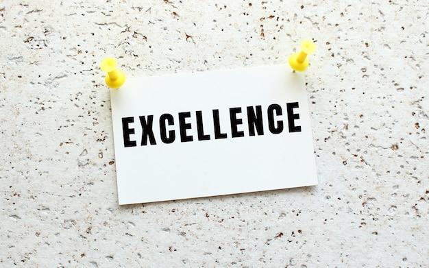 Eccellenza è scritto su una carta attaccata a un muro bianco strutturato con un pulsante. promemoria d'ufficio. concetto di affari.
