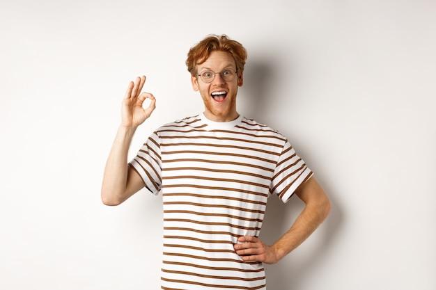 Lavoro eccellente. uomo rosso felice che ti elogia, mostra il segno ok e sorride stupito, approva e gradisce qualcosa di buono, in piedi su sfondo bianco.