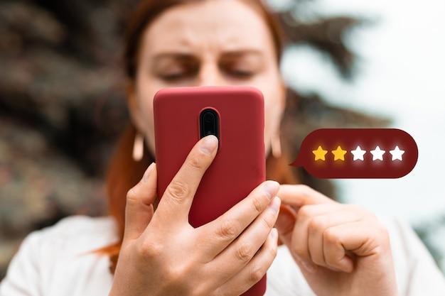 Eccellente. persona che utilizza il telefono cellulare con l'icona simbolo a due stelle per aumentare la valutazione dell'azienda, concetto di servizio clienti