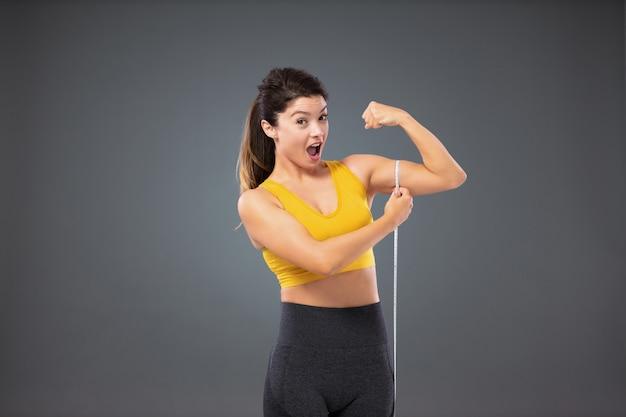Risultati eccellenti per una vita, un allenamento e una dieta sani. montare la donna in abbigliamento sportivo davanti a un muro grigio che misura la circonferenza del suo braccio con un nastro. soddisfatto di una perfetta muscolatura del corpo e delle braccia