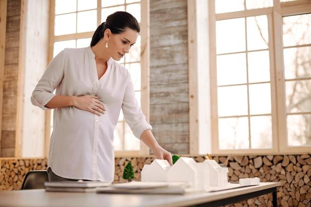 Vista eccellente. attraente designer incinta professionista che accarezza la pancia mentre guarda la modella e sorride