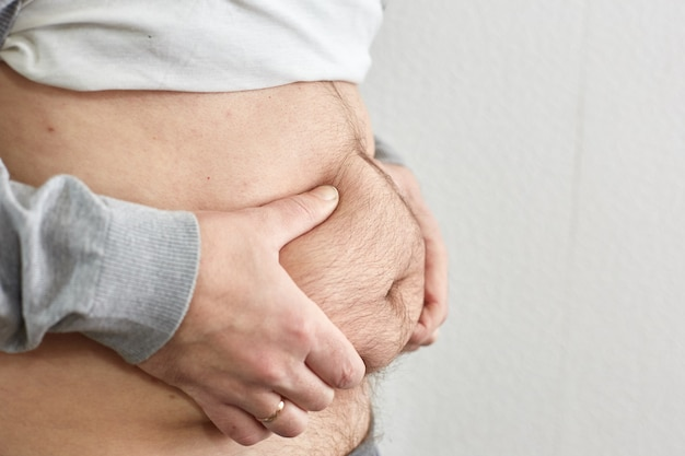 Eccesso di grasso sull'addome maschile, scarsa forma fisica a causa di un'alimentazione scorretta.